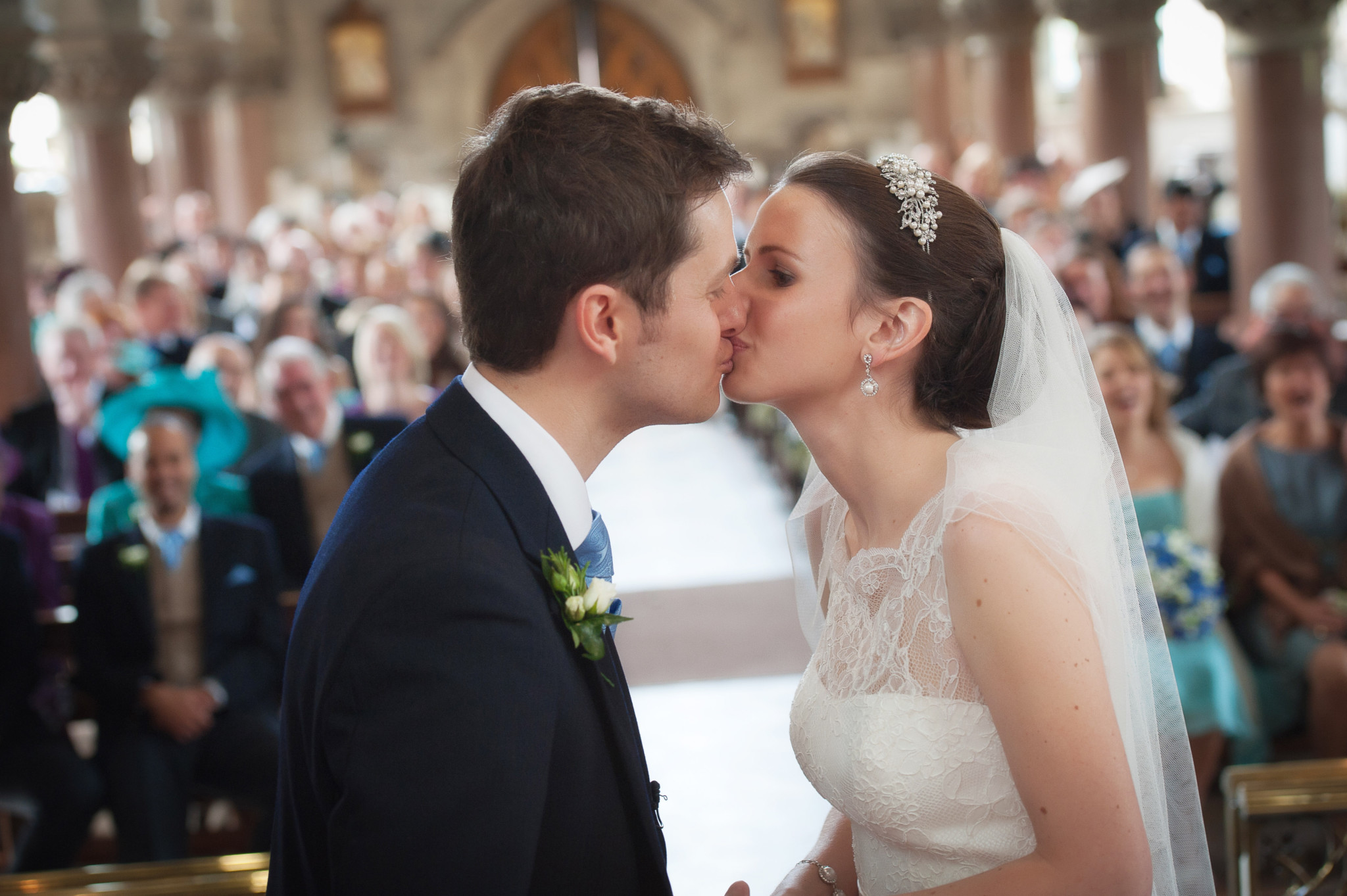 Wedding photograph of the couple kissing in church