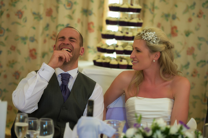 Wedding photograph of the groom laughing at the reception