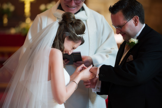 Wedding photograph of bride trying to put the ring on
