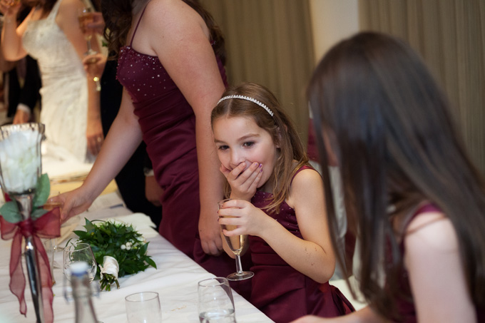 Wedding photograph of bridesmaid having a sip of champagne