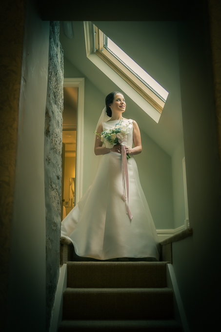 Wedding photography - bride on stairs looking through window