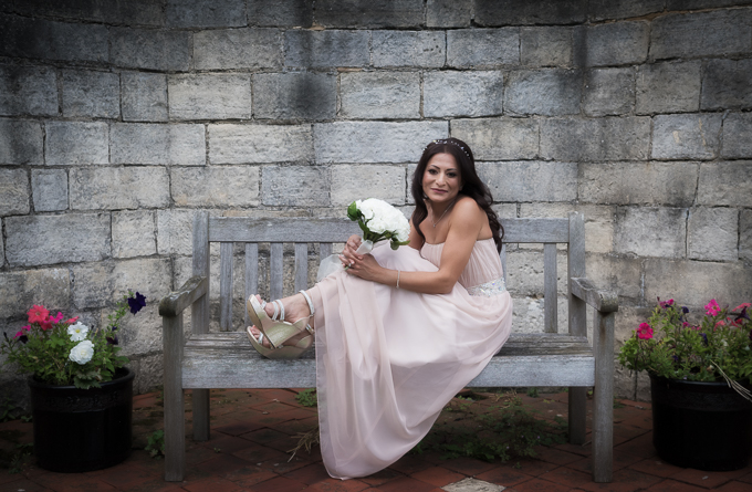 Wedding photography - bride sitting on a park bench