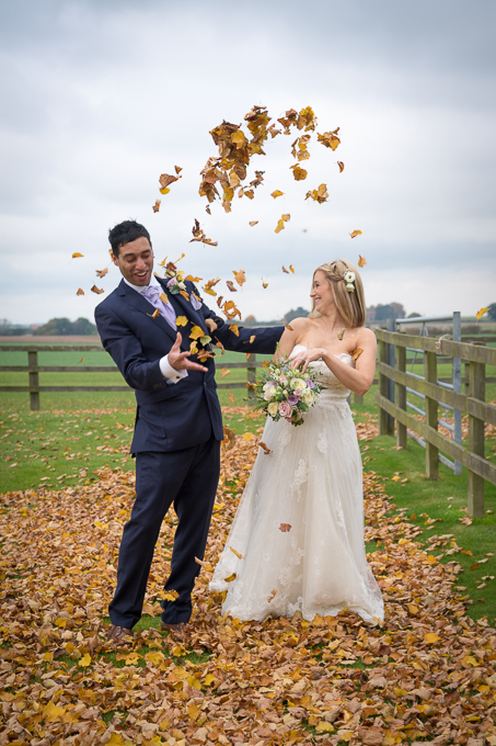 Wedding photography - bride and groom throwing leaves in the air