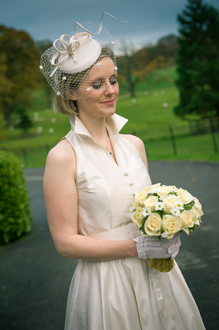 Wedding photograph - the bride looking down at her bouquet of yellow roses