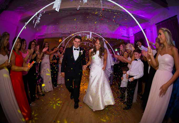 Wedding Photography - couple walking under confetti