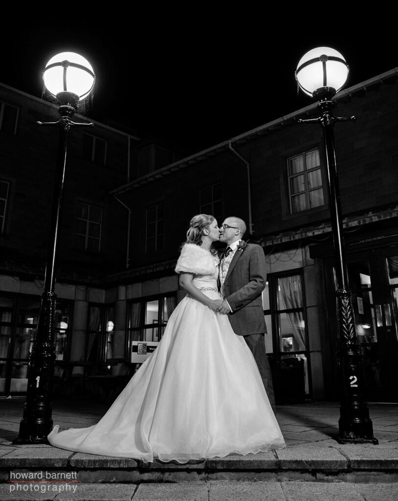 Wedding Weetwood Hall Leeds - couple kissing under lamplights